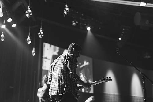 grey grayscale photo of man playing electric guitar stage
