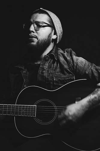 human grayscale photo of man playing guitar people