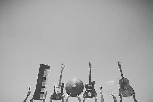 guitar grayscale photo of people holding assorted music instruments grey