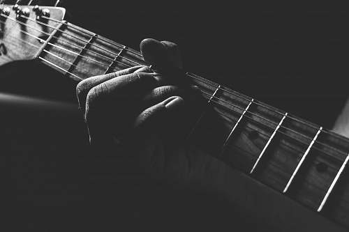 grey grayscale photo of person holding guitar neck and strings guitar