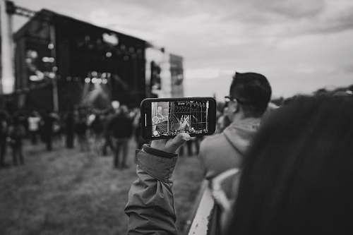 human grayscale photo of person holding smartphone person
