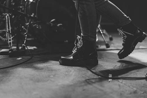 footwear person in black leather boots walking beside of drum set clothing