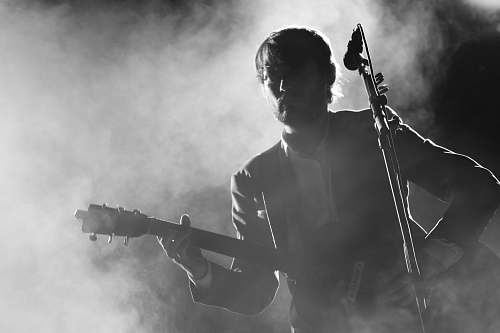 human silhouette of man playing a guitar beside a microphone people