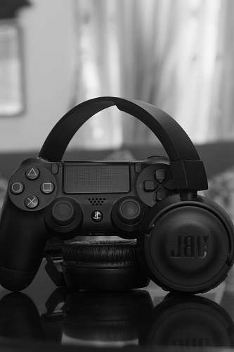 grey Sony PS DualShock 4 beside JBL wireless headphones camera
