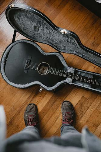 clothing person taking picture of black classic guitar inside black and gray guitar case cowboy boot