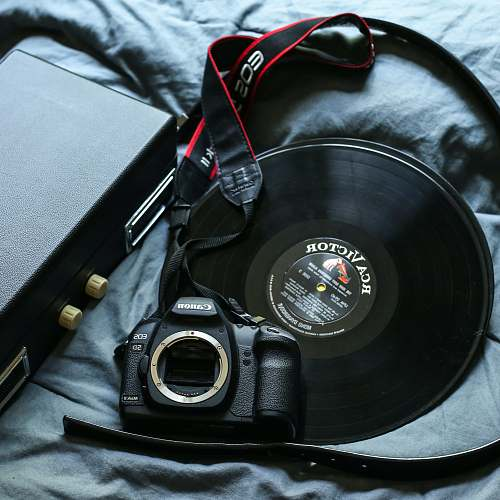 electronics black Canon EOS 5D DSLR camera beside black RCA Victor vinyl record lifestyle
