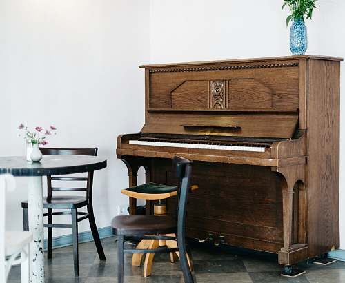 furniture brown piano in front of white wall table
