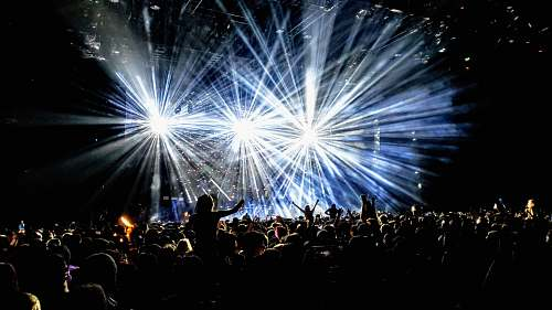 person time lapse photography of group of people facing on stage lighting
