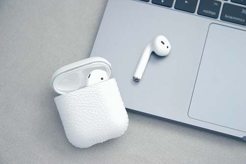 macbook white Apple AirPods beside MacBook Pro earphone