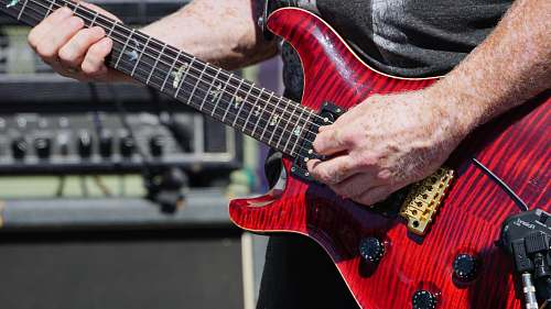guitar person playing a red stratocaster guitar during daytime leisure activities