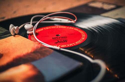 wristwatch closeup photo of earbuds on LP records headphones