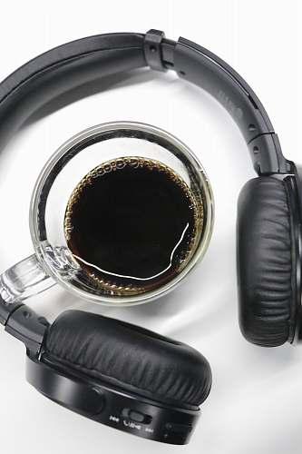 headphones half-filled clear glass cup in black wireless headphones headset