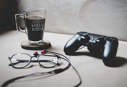 drink black Sony Dualshock 4 beside clear glass mug filled with coffee istanbul