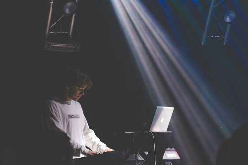 human man in white sweater playing electronic keyboard person