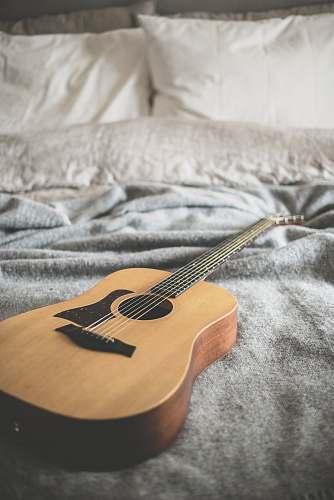 music brown acoustic guitar on gray blanket grey