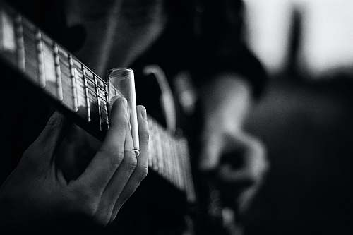 black-and-white grayscale photography of person playing guitar music