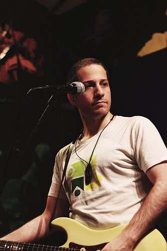 human man wearing white shirt playing guitar person