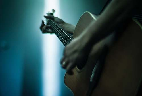 music person playing acoustic guitar shallow focus photography musical instrument