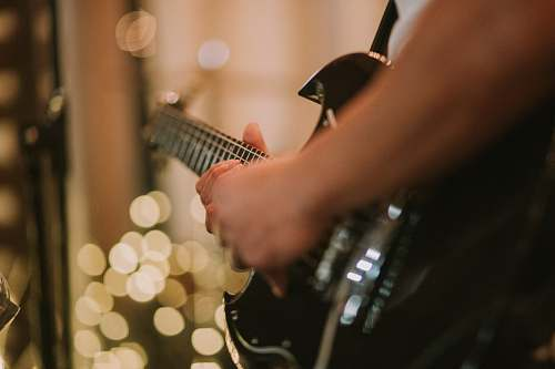 bokeh person playing black SG guitar hands