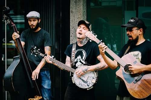 music three men playing stringed instruments during daytime musician