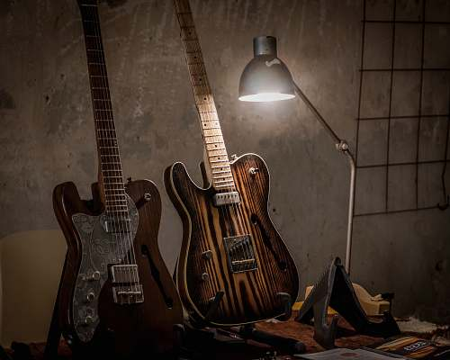 leisure activities two brown guitars beside desk lamp electric guitar