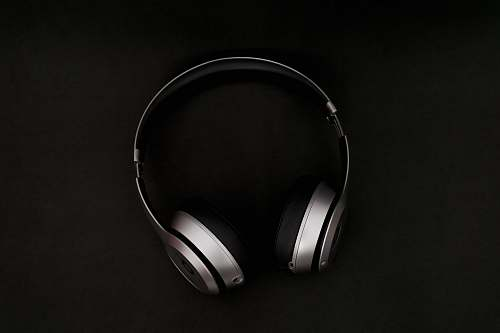 black-and-white silver headphones on top of black surface black