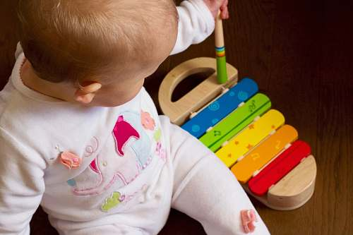 people baby playing multicolored xylophone toy person