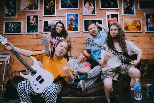 person band taking groufie picture on brown sofa people