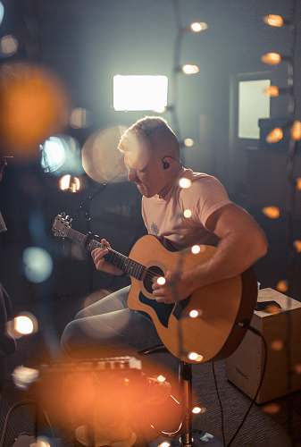 person bokeh photography of man playing guitar people