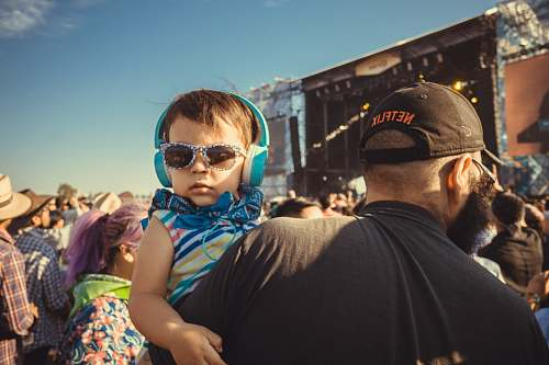 person boy carrying a girl wearing sunglasses and headphones apparel
