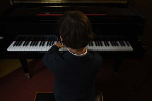 person boy playing a piano performer