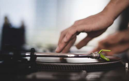 person close-up photo of person using turntable hand