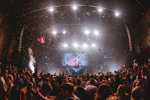 person confetti falling from above at music performance with huge crowd crowd