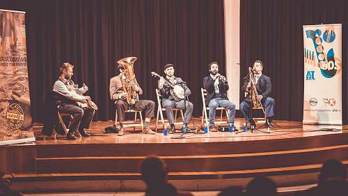 person five men playing instruments on stage people