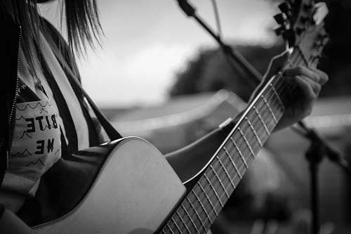 person grayscale and selective focus photography of woman playing guitar black-and-white