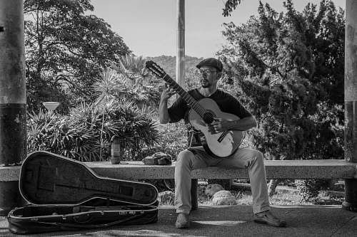 people grayscale photography of man playing classic guiar black-and-white