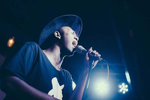 person low angle of man wearing cap singing in microphone people