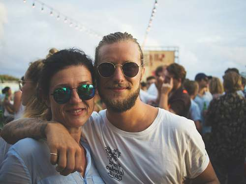 person man and woman smiling on focus photography sunglasses