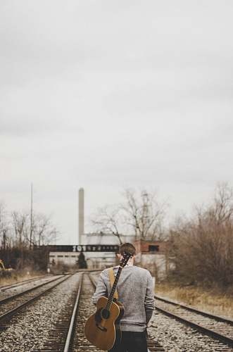 person man carrying guitar walking on train rails people