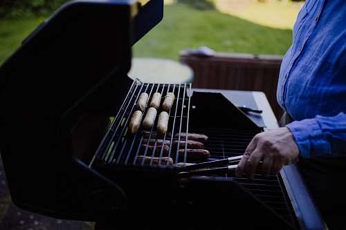 person man grilling sausage during daytime people