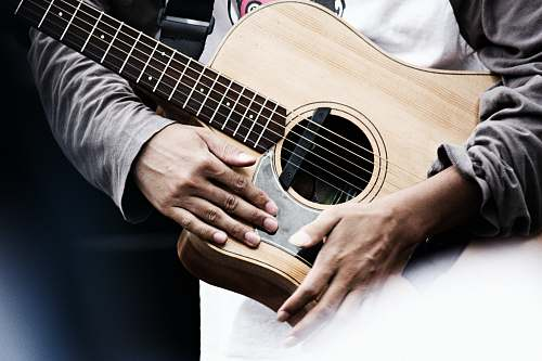 person man holding acoustic guitar people