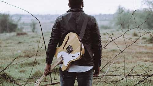 person man holding brown guitar people