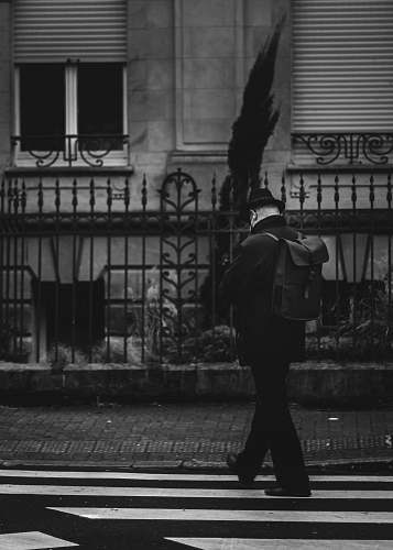 person man in black jacket walking on sidewalk black-and-white