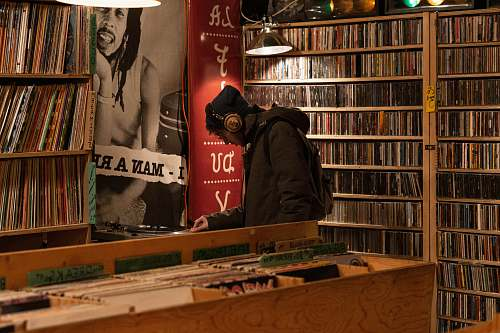 furniture man in hoodie and headphones standing inside record store shelf