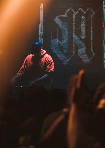 person man in red hoodie with headphones operating DJ mixer machine crowd