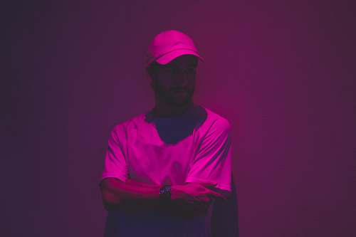 person man leaning of wall with purple light in fashion photography people