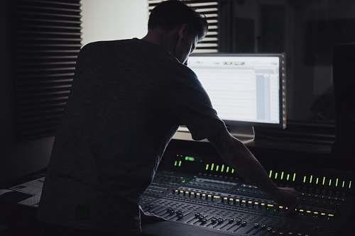 person man operating audio mixer studio