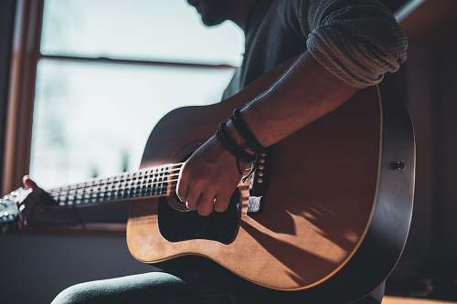 person man playing acoustic guitar selective focus photography people