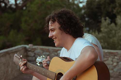 people man playing acoustic guitar while smiling person