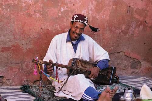 person man playing brown guitar guitar